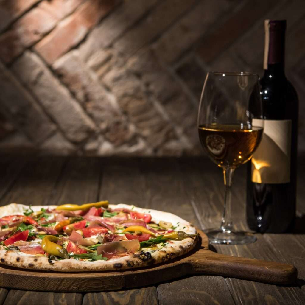 selective focus of italian pizza, bottle and glass of wine on wooden tabletop
